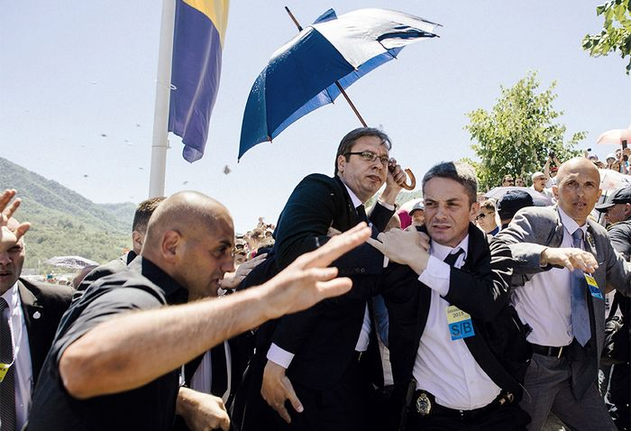 TOPSHOTS Bodyguards try to protect Serbian Prime Minister Aleksandar Vucic (C) from stones hurled at him by an angry crowd at the Potocari Memorial Center, near the eastern Bosnian town of Srebrenica on July 11, 2015. Tens of thousands of people gathered in Srebrenica on July 11 to commemorate the 20th anniversary of the massacre of thousands of Muslims in the worst mass killing in Europe since World War II. Serbian Prime Minister Aleksandar Vucic was forced to leave the Srebrenica memorial when the crowd started to chant 'Allahu Akbar' (God is Great) and to throw stones. AFP PHOTO / DIMITAR DILKOFF