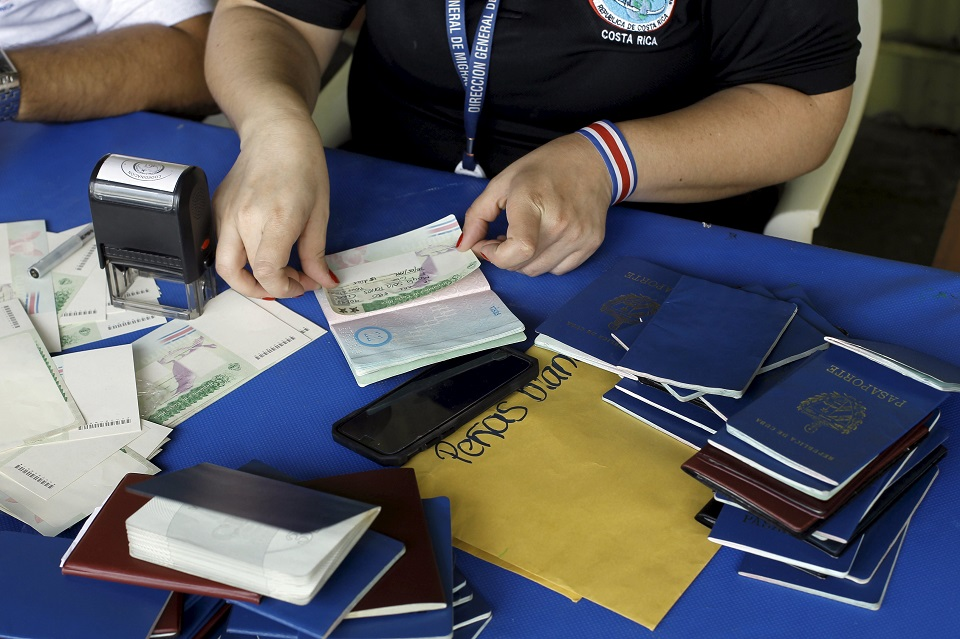 A Costa Rican immigration officer sticks a visa extension to last for 15 more days into a Cuban passport in Liberia, Costa Rica, November 26, 2015. Thousands of Cubans remain stuck on the Costa Rican side of the border with Nicaragua after Managua refused at a regional summit on Tuesday to open its doors to a wave of migrants heading for the United States. Fearing the recent rapprochement between Havana and Washington could end preferential U.S. policies for Cuban migrants, thousands of people from the Communist-ruled island have been crossing into South America and traveling through Central America hoping to reach U.S. soil.   REUTERS/Juan Carlos Ulate